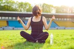 Der von mittlerem Alter übendes Yoga Frau im Stadion Stockbilder