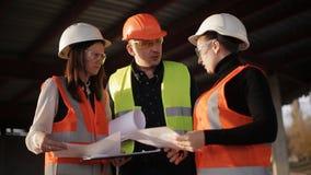 Der Vorarbeiter erklärt den zwei Frauen Inspektoren auf dem Fortschritt von Bauarbeiten stock video
