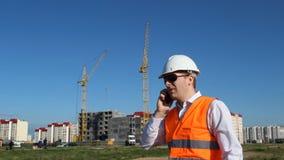 Der Vorarbeiter spricht am Telefon auf dem Hintergrund des Baus eines Apartmenthauses stock video footage