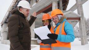 Der Vorarbeiter und der Inspektor mit zwei Frauen im Winter, kontrollieren die Baustelle, die hinter ihnen im Hintergrund gelegen stock footage