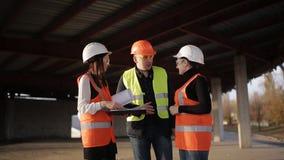 Der Vorarbeiter und zwei Fraueninspektoren, welche die Baustelle besichtigen stock footage