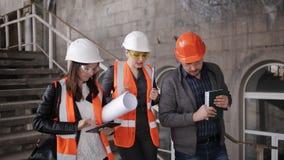 Der Vorarbeiter und zwei Fraueninspektoren, welche die Baustelle besichtigen stock video footage
