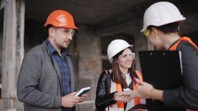 Der Vorarbeiter und zwei Fraueninspektoren, welche die Baustelle besichtigen stock video