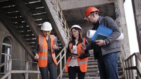 Der Vorarbeiter und zwei Fraueninspektoren, zum des Arbeitsplans zu besprechen durchgeführt am Bau oder an der Wiederherstellung  stock footage