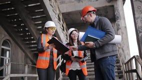 Der Vorarbeiter und zwei Fraueninspektoren, zum des Arbeitsplans zu besprechen durchgeführt am Bau oder an der Wiederherstellung  stock video footage