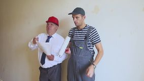 Der Vorarbeiter weist den Malererbauer, sie besprechen die Details der Reparatur an Älterer Betriebsleiter und Junge stock footage