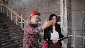 Der Vorarbeiter zeigt einem weiblichen Ingenieur die Arbeitslast erfordert auf der Baustelle stock footage