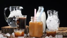 Der Würfel des Eises unten fallend in heißen Kaffee mit hellem spritzt in der Zeitlupe Brown-Thema Foodart schoss von der Werbung stock video