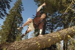 Der Wanderer springend über gefallenen Baum im Wald Stockfotos