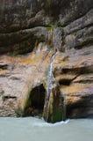 Der Wasserfall fließt hinunter einen dünnen Strom über einem Felsen und fällt in einen Gebirgsfluss lizenzfreie stockfotos