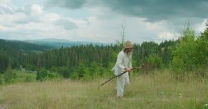 Der Weg des alten grauen Mannes in der alten Kleidung, die den Stock hält Die ausgezeichnete Ansicht der grünen Berge stock video footage