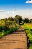 Der Weg im Park, der zu einen Abstand, mit einem blauen Himmel und einem grünen Gras führt Fanari entlang der Straße, die in eins Stockbilder