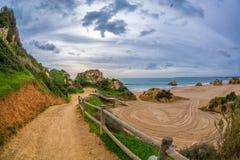 Der Weg unter den Felsen und den grünen Hügeln, die zu den berühmten Strand in Alvor, Algarve, Portugal führen stockbilder