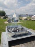 Der Wegwerfgrill am Picknicktisch Stockfoto