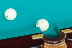 Der weiße Ball auf dem grünen Segeltuch fällt in die Tasche der Tabelle Stockbilder
