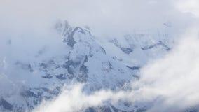 Der weiße Berg, der mit Schnee bedeckt wird, glänzt durch eine schöne weiße Wolke Stockbild