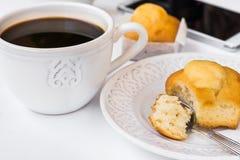 Der weiße Desktop mit Tasse Kaffee, Platte mit Muffin und Smartphone, redete Bild für Social Media an Lizenzfreie Stockfotografie