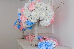 Der weiße Kamin wird mit Kerzen und Blumen verziert lizenzfreies stockbild