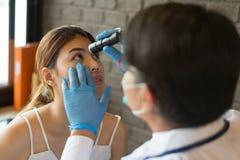 Der weiße Mantel Doktorabnutzung glänzt eine Taschenlampe an den Augen eines weiblichen Patienten an einer Klinik Konzept des Ges lizenzfreies stockbild