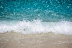 Der weiße Schaumreiniger schlug die Küste mit sehr feinem Sand Stockfoto