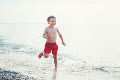 Der weißer junger kleiner Junge des Kaukasiers in den roten Schwimmenkurzen hosen, die auf Strand durch Wasser laufen Stockbilder