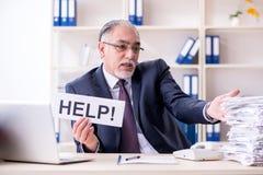 Der weiße bärtige alte Geschäftsmannangestellte unglücklich mit übermäßiger Arbeit lizenzfreie stockfotos