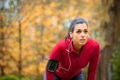 Der weibliche Athlet, der einen Betrieb nimmt, arbeiten Rest aus Stockfotografie