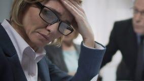 Der weibliche Büroangestellte, der bei der Konferenz gestört wird, glaubt Kopfschmerzen, dem Chef, der über Ausfallung verärgert  stock video footage