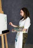 Der weibliche Farbenkünstler, der nahe bei einem Gestell und Farben auf einem Segeltuch aufwirft, stellt eine Träumerei dar Lizenzfreie Stockfotografie