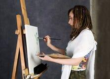 Der weibliche Farbenkünstler, der nahe bei einem Gestell und Farben auf einem Segeltuch aufwirft, stellt eine Träumerei dar Stockfoto