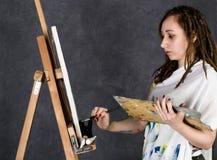 Der weibliche Farbenkünstler, der nahe bei einem Gestell und Farben auf einem Segeltuch aufwirft, stellt eine Träumerei dar Stockbild