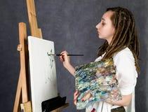 Der weibliche Farbenkünstler, der nahe bei einem Gestell und Farben auf einem Segeltuch aufwirft, stellt eine Träumerei dar Lizenzfreies Stockbild