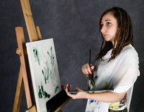 Der weibliche Farbenkünstler, der nahe bei einem Gestell und Farben auf einem Segeltuch aufwirft, stellt eine Träumerei dar Lizenzfreie Stockfotos