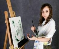 Der weibliche Farbenkünstler, der nahe bei einem Gestell und Farben auf einem Segeltuch aufwirft, stellt eine Träumerei dar Lizenzfreies Stockfoto