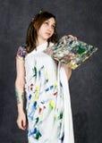 Der weibliche Farbenkünstler, der nahe bei einem Gestell und Farben auf einem Segeltuch aufwirft, stellt eine Träumerei dar Lizenzfreie Stockbilder
