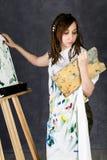 Der weibliche Farbenkünstler, der nahe bei einem Gestell und Farben auf einem Segeltuch aufwirft, stellt eine Träumerei dar Stockfotos