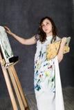 Der weibliche Farbenkünstler, der nahe bei einem Gestell und Farben auf einem Segeltuch aufwirft, stellt eine Träumerei dar Stockfotografie