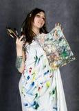 Der weibliche Farbenkünstler, der nahe bei einem Gestell und Farben auf einem Segeltuch aufwirft, stellt eine Träumerei dar Stockbilder