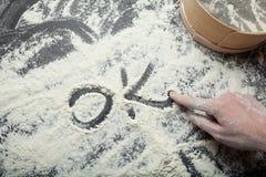 Der weibliche Finger schreibt das 'okay'Wort auf Weißmehl Das Konzept des selbst gemachten Backens lizenzfreies stockbild