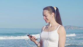 Der weibliche gehende Rüttler und hören Musik auf dem Strand stock video footage