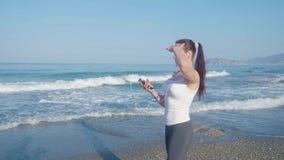 Der weibliche gehende Rüttler und hören Musik auf dem Strand stock footage