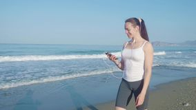 Der weibliche gehende Rüttler und hören Musik auf dem Strand stock video