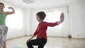 Der weibliche Lehrer des schönen Sitzes, der ein kleines Mädchen noch steht Yoga unterrichtet, wirft in der Zeitlupe in einem hel stock footage