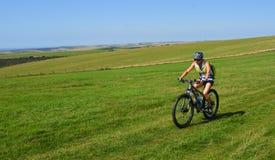 Der weibliche Mountainbiker, der die Süd- Abstiege reitet, nähern sich BO-Blick-Hügel Ost-Sussex lizenzfreies stockbild
