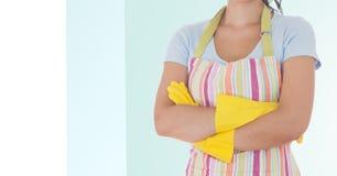 Der weibliche Reiniger, der mit den Armen steht, kreuzte tragende Schutzblech- und Gummihandschuhe Stockfoto