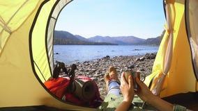 Der weibliche Reisende liegt in einem gelben Zelt Die Frau hält eine Tasse Tee in der Hand Ansicht des Gebirgssees stock video footage