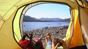 Der weibliche Reisende liegt in einem gelben Zelt Die Frau hält eine Tasse Tee in der Hand Ansicht des Gebirgssees Dann stock footage