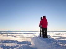 Der weibliche Skifahrer, der heraus über Wolke schaut, deckte Tal ab Stockfoto