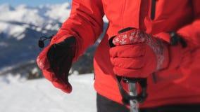 Der weibliche Skifahrer, der Handschuhe und Skischutzbrillen trägt, nimmt seine Skipfosten und Anfänge hinunter den Hügel stock video