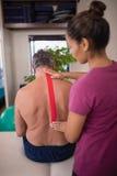 Der weibliche Therapeut, der elastisches therapeutisches Band unterstützen anbringt an, vom hemdlosen älteren männlichen Patiente stockfotos